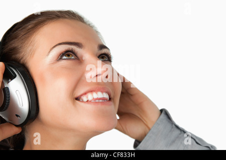 Close up of young businesswoman listening to music - Stock Photo