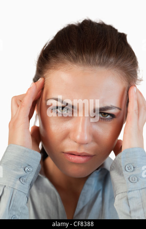 Close up of young businesswoman suffering from a headache - Stock Photo