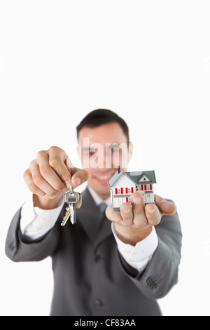 Miniature house and keys being presented by male estate agent - Stock Photo
