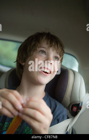 Eight year old boy looking our of car window with expression of wonder and amazement. - Stock Photo