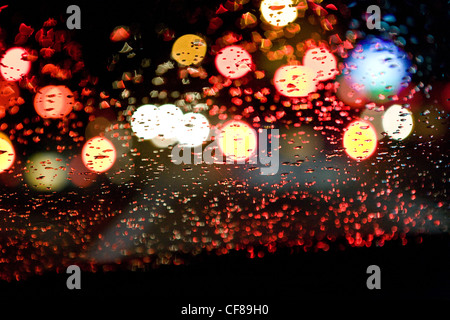 view through wet car windshield, traffic, night, city. - Stock Photo