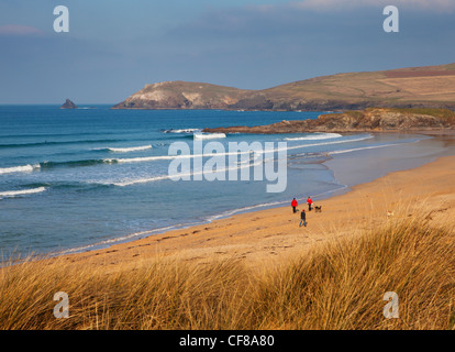 People walking on Constantine Bay in Cornwall on a sunny winter's day. - Stock Photo
