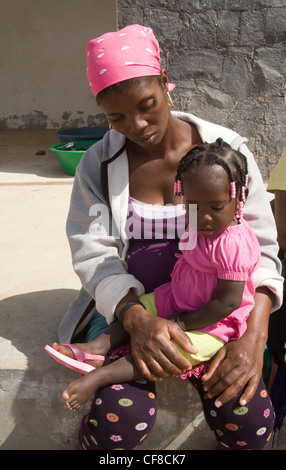 Cape Verde Islands Young mother baby girl braided hair with pink beads sitting on lap - Stock Photo