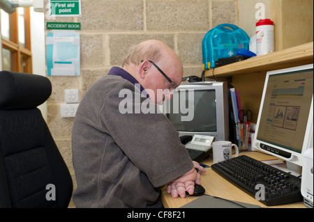 A disabled male with multiple congenital deformities working on the telephone helpline at the headquarters of Disability - Stock Photo
