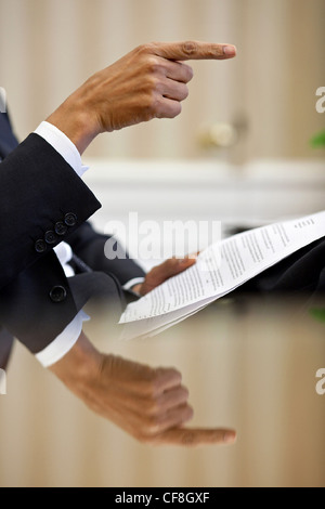 President Barack Obama hand is reflected on his desk as he gestures during a speech prep meeting in the Oval Office - Stock Photo