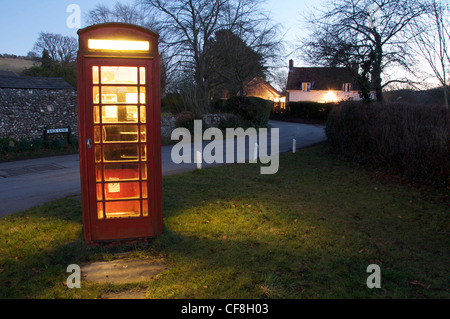 The light from a traditional red telephone box illuminates a dark and lonely country lane in the Dorset village - Stock Photo