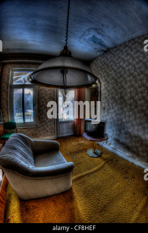 Interior of disused hotel near East German border with grey interior sofa television and ceiling light - Stock Photo