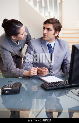Businesswoman explaining something to her colleague - Stock Photo