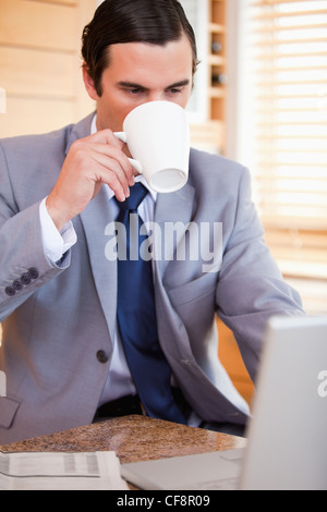 Businessman taking a sip of coffee next to his laptop - Stock Photo