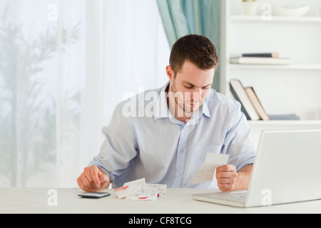 Businessman calculating his expenses - Stock Photo