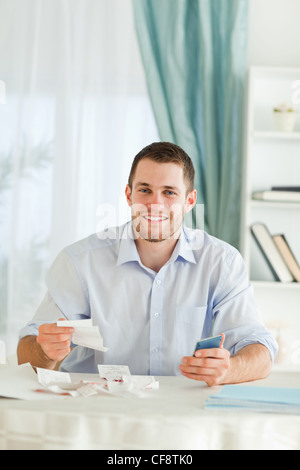 Businessman with hand calculator checking invoices - Stock Photo