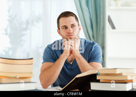 Student sitting at his desk in thoughts - Stock Photo