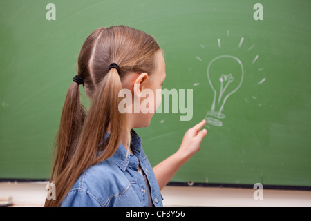 Schoolgirl pointing at a bulb - Stock Photo