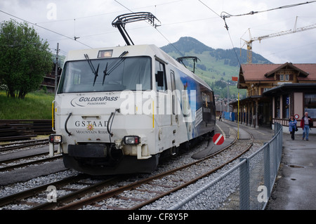 Golden Pass Panoramic express passing Montbovon station. Montreux-Oberland Bernois railway one of oldest electric - Stock Photo