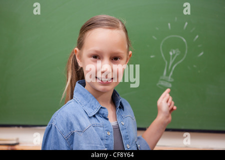 Smiling schoolgirl pointing at a bulb - Stock Photo