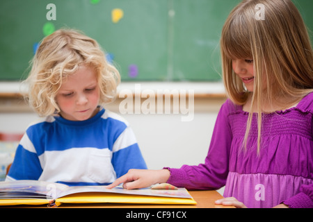 Pupils reading a book - Stock Photo