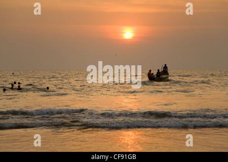 GOA, INDIA - 19 NOV 2011: indian boat and swimming children at sunset in the seaon Arambol beach in Goa - Stock Photo