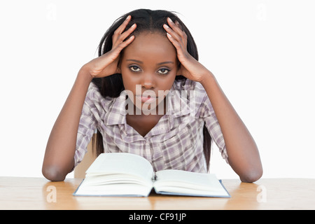 Bored student trying to read a book - Stock Photo
