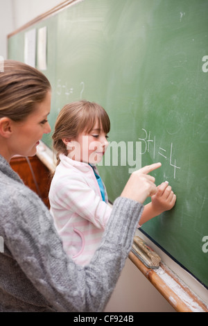 Portrait of a teacher and a pupil making an addition - Stock Photo