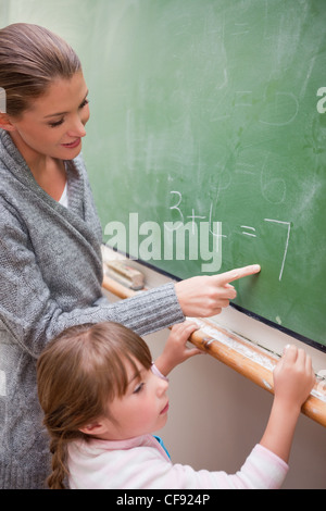 Portrait of a happy teacher and a pupil making an addition - Stock Photo