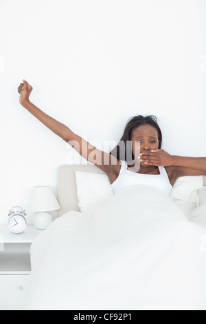 Portrait of a woman stretching her arms while yawning - Stock Photo