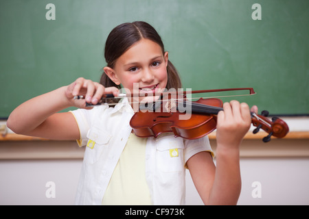 Smiling schoolgirl playing the violin - Stock Photo