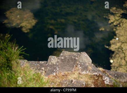 The view of the climbing rock from the top of the cliff looking down into the loch at Auchinstarry Quarry, Scotland - Stock Photo