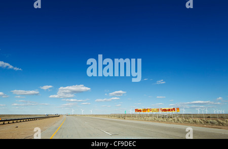 A big sky over Interstate 80 in southern Wyoming in early spring, with a wind farm on the horizon. - Stock Photo