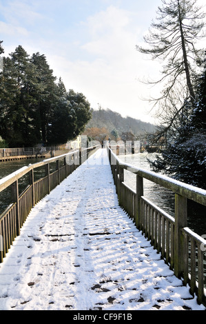 Man and woman walking over snow covered footbridge over River Thames, at Marsh Lock, Henley-on-Thames, Berkshire, - Stock Photo