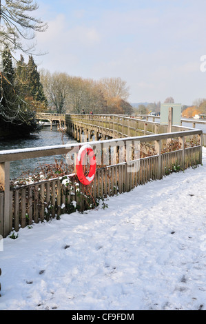 Snow covered footbridge over River Thames, at Marsh Lock, Henley-on-Thames, Berkshire, England looking downstream - Stock Photo