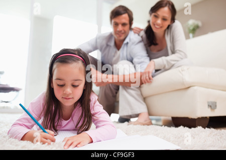 Little girl drawing with her parents in the background - Stock Photo