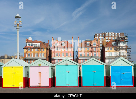 Brightly coloured beach huts on Brighton & Hove seafront with period buildings behind - Stock Photo