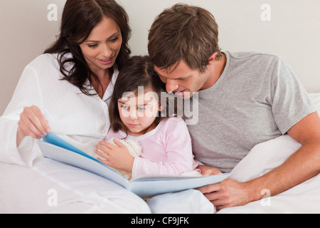 Parents reading a story to their daughter - Stock Photo