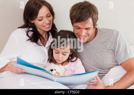 Happy parents reading a story to their daughter - Stock Photo