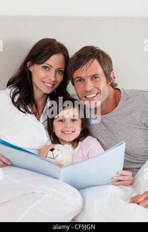 Portrait of parents reading a story to their daughter - Stock Photo