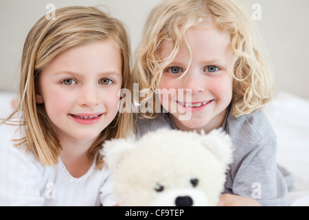 Siblings lying on the bed with their teddy - Stock Photo