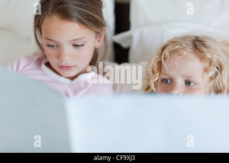 Girl reading a bed time story for her brother - Stock Photo