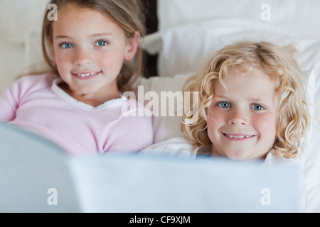Siblings enjoy reading bed time story - Stock Photo