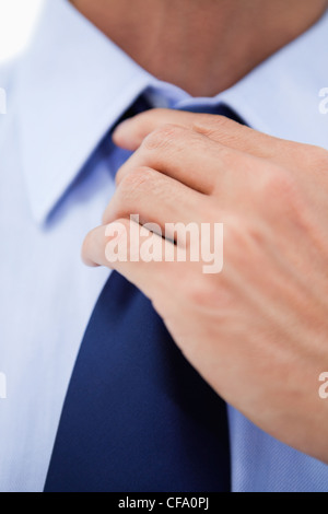 Close up of a businessman fixing his tie - Stock Photo