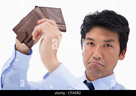 Businessman showing his empty wallet - Stock Photo