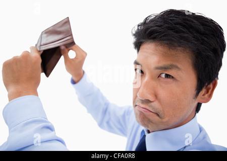 Broke businessman showing his empty wallet - Stock Photo