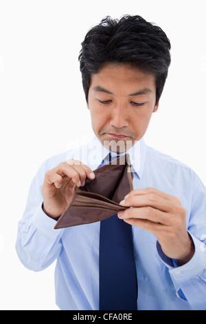 Portrait of a sad businessman showing his empty wallet - Stock Photo
