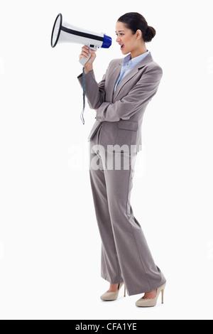 Portrait of a businesswoman shouting through a megaphone - Stock Photo