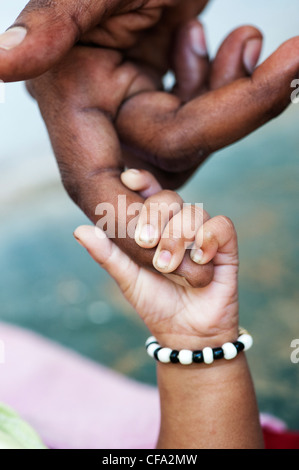 Indian mans hand holding his new born babies hand. Andhra Pradesh, India Stock Photo