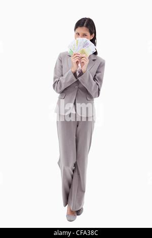 Businesswoman hiding face behind bank notes - Stock Photo