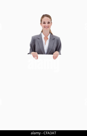 Bank employee holding blank sign in her hands - Stock Photo
