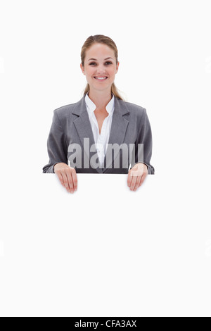 Smiling bank employee holding blank sign in her hands - Stock Photo