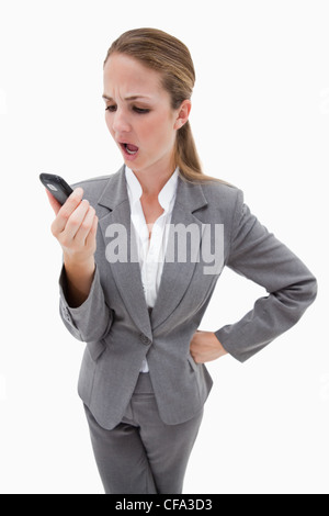 Indignant looking bank employee reading text message - Stock Photo