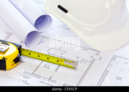 Still life photo of some building plans with a hard hat and tape measure. - Stock Photo