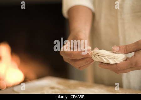 Cook folding filled pasta in kitchen - Stock Photo